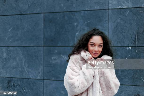 portrait of smiling woman against wall - winter coat stock pictures, royalty-free photos & images