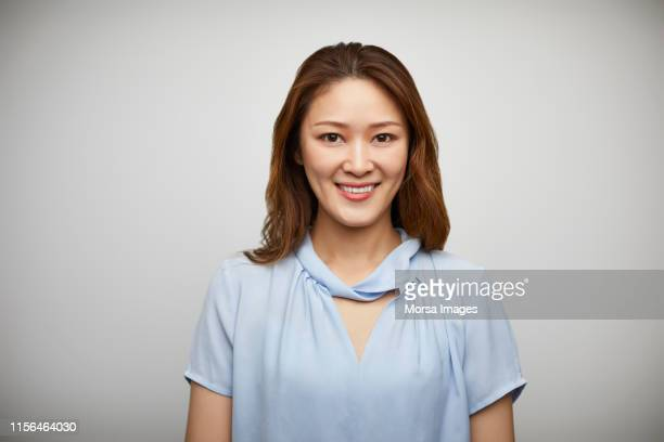 portrait of smiling woman against white background - mid length hair stock pictures, royalty-free photos & images