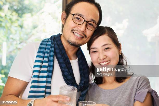 portrait of smiling woman and man wearing glasses standing side by side, looking at camera. - 夫婦 ストックフォトと画像