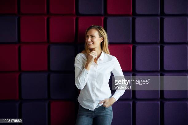 portrait of smiling woman at a purple wall - blouse stock pictures, royalty-free photos & images