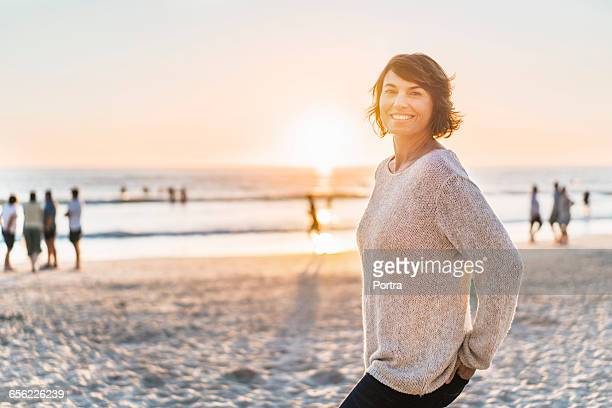 Portrait of smiling woman at beach during sunset