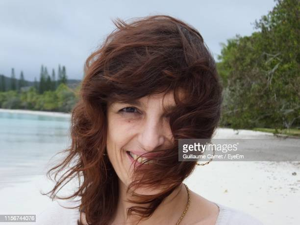 portrait of smiling woman at beach - carnet stock photos and pictures