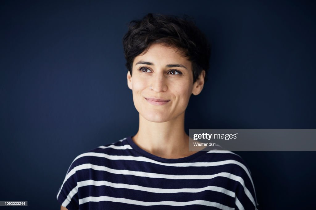 Portrait of smiling woman at blue wall : Photo