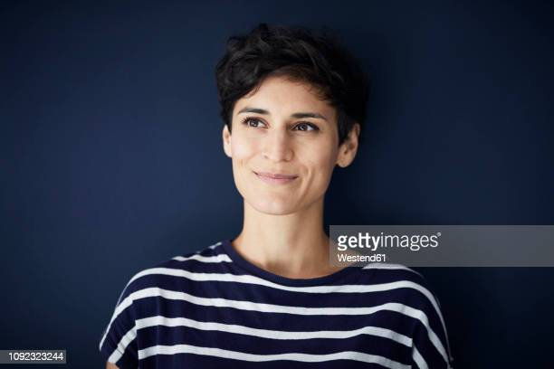 portrait of smiling woman at blue wall - frau stock-fotos und bilder