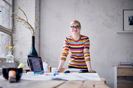 Portrait of smiling woman at desk in a loft - gettyimageskorea