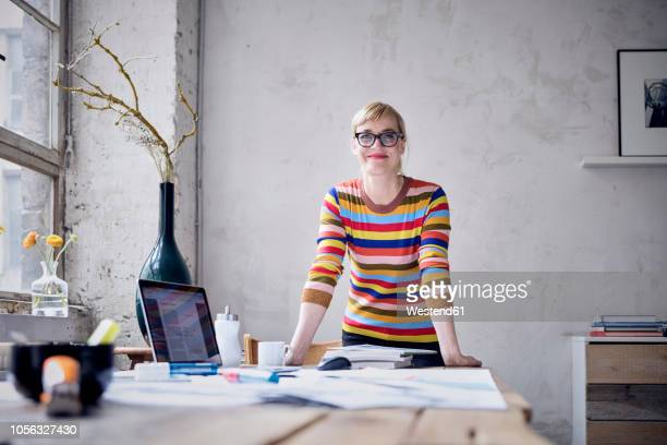 portrait of smiling woman at desk in a loft - unabhängigkeit stock-fotos und bilder