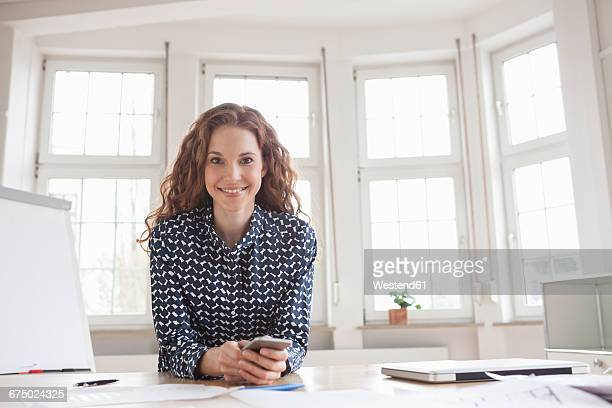 Portrait of smiling woman at desk in office