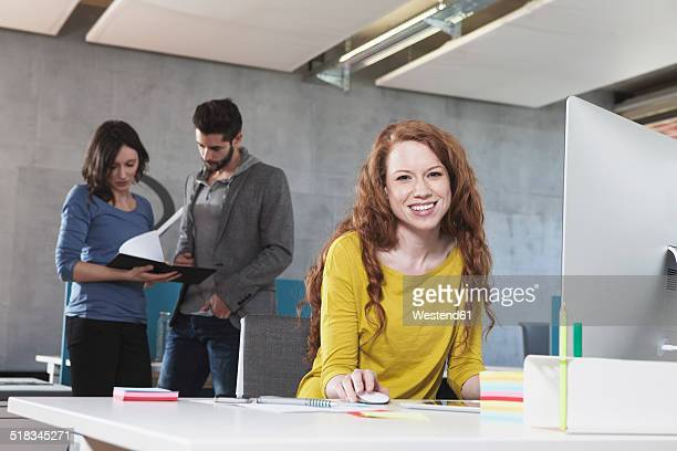 Portrait of smiling woman at her workplace in the office