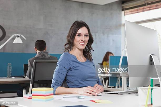 Portrait of smiling woman at his workplace in the office