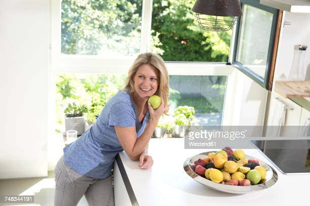 Portrait of smiling woman at home eating an apple