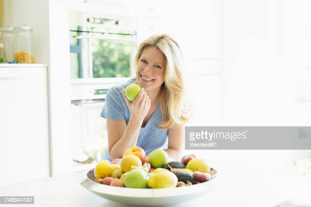 portrait of smiling woman at home eating an apple - apple fruit stock photos and pictures
