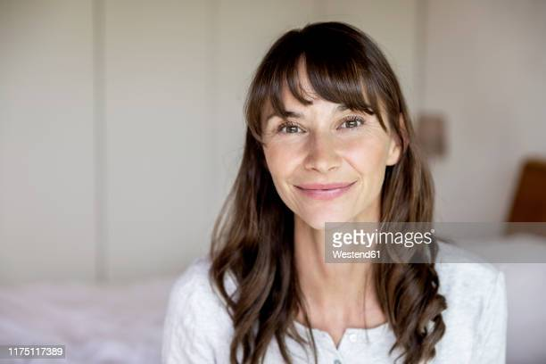 portrait of smiling woman at home - brown hair stock pictures, royalty-free photos & images