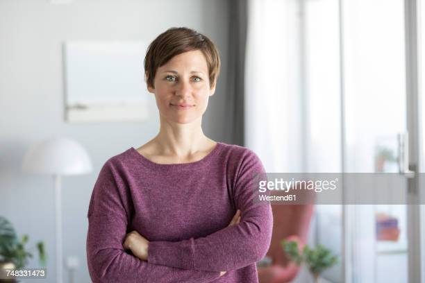 portrait of smiling woman at home - mid adult woman sweater stock pictures, royalty-free photos & images