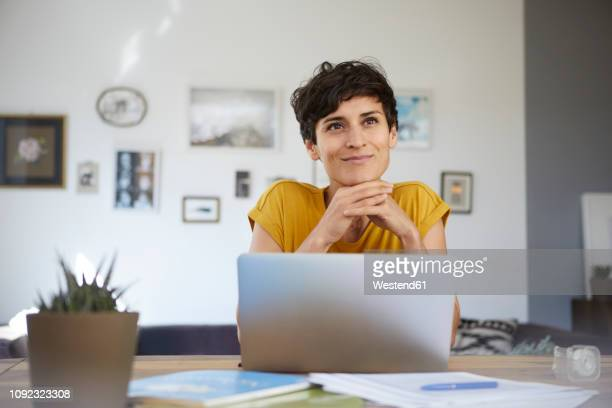portrait of smiling woman at home sitting at table using laptop - distrarre lo sguardo foto e immagini stock