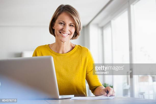 Portrait of smiling woman at home using laptop