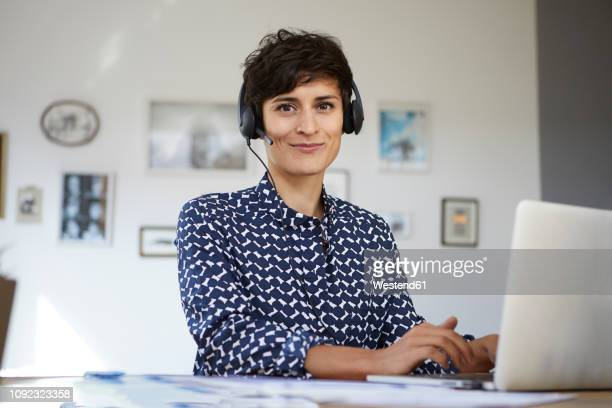 portrait of smiling woman at home with headset and laptop - adults only stock pictures, royalty-free photos & images