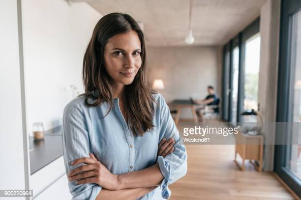portrait of smiling woman at home with man in background - arme verschränkt stock-fotos und bilder