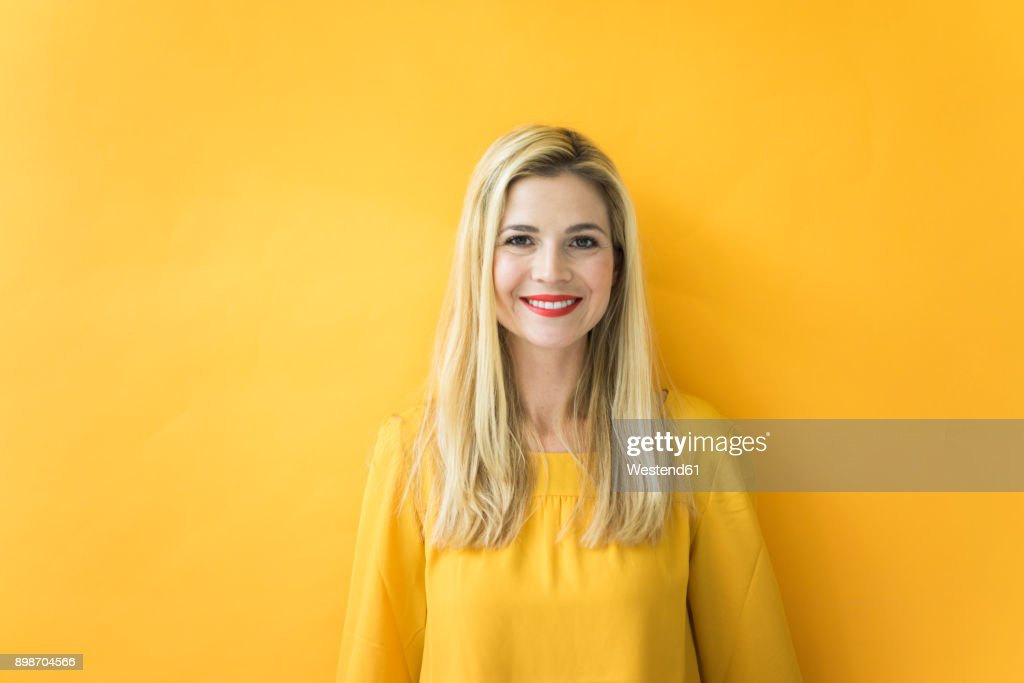 Portrait of smiling woman at yellow wall : Stock Photo