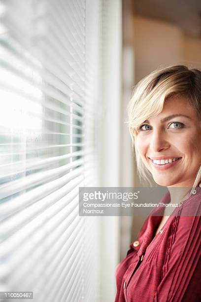 portrait of smiling woman beside an office window - cef do not delete stock pictures, royalty-free photos & images