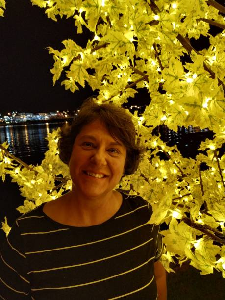 Portrait Of Smiling Woman By Illuminated Tree At Night