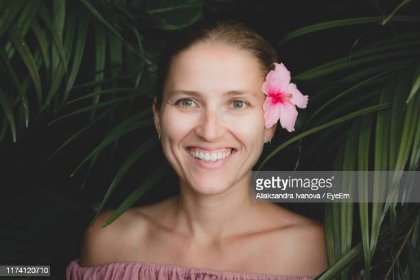 portrait of smiling woman by plants - tahiti stock pictures, royalty-free photos & images