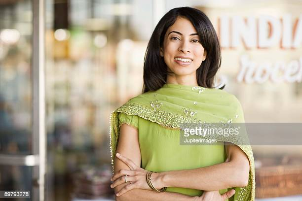 Portrait of smiling woman by storefront