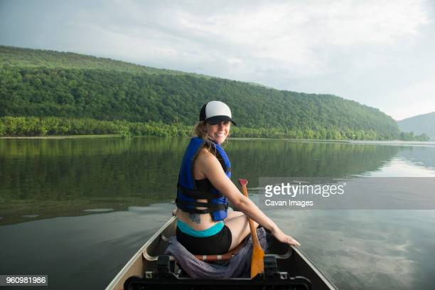 portrait of smiling woman canoeing on river against cloudy sky - harrisburg pennsylvania stock pictures, royalty-free photos & images