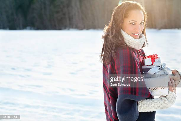 Portrait of smiling woman carrying Christmas gifts in snow