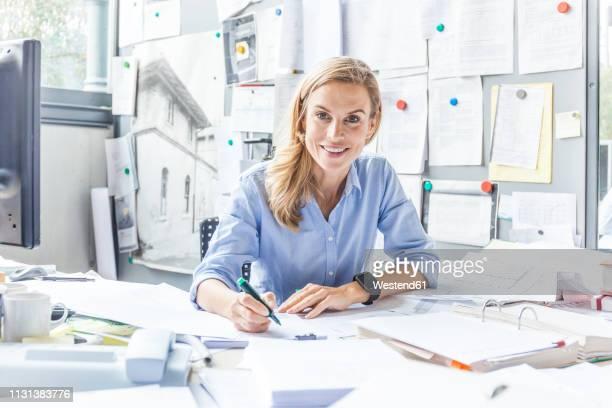 portrait of smiling woman doing paperwork at desk in office - ingeniero civil fotografías e imágenes de stock