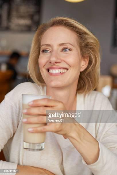 Portrait of smiling woman drinking Latte Macchiato in a coffee shop