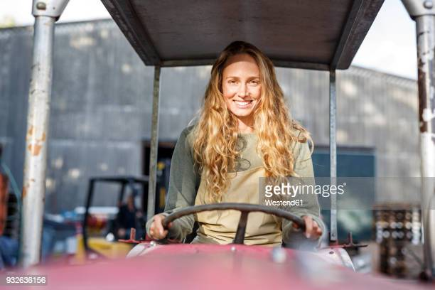 Portrait of smiling woman driving a tractor
