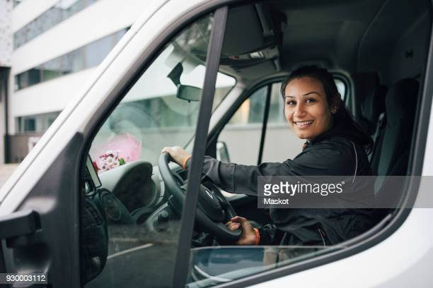 portrait of smiling woman driving delivery van in city - delivery person stock pictures, royalty-free photos & images
