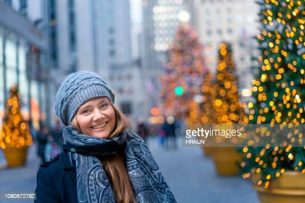 porträt der lächelnde frau in der weihnachtszeit in stadt - new york weihnachten stock-fotos und bilder