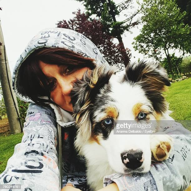 Portrait Of Smiling Woman Embracing Dog At Park
