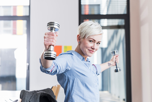 Portrait of smiling woman exercising with dumbbells in office - gettyimageskorea
