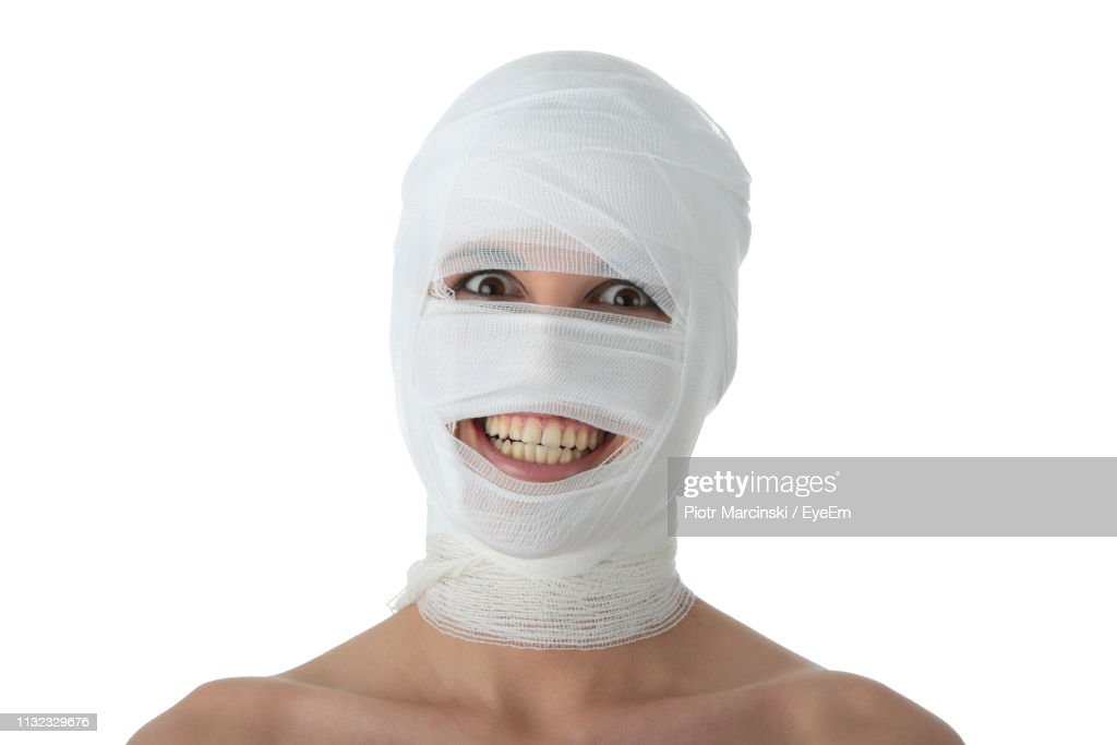 Portrait Of Smiling Woman Face Wrapped In Bandage Against White Background : Stock Photo