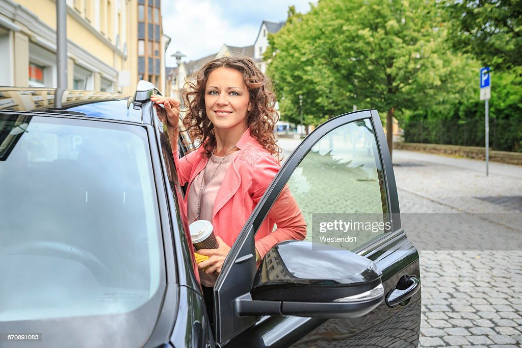 Portrait of smiling woman getting on her car : Photo