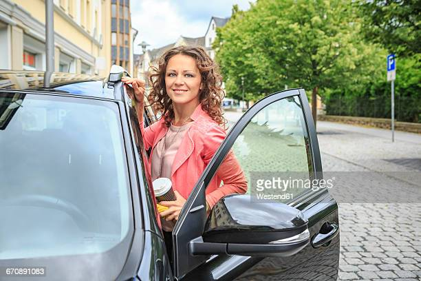 Portrait of smiling woman getting on her car