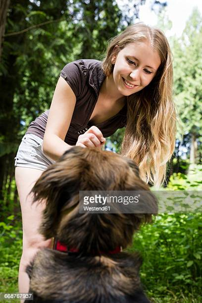 Portrait of smiling woman giving her mongrel a treat