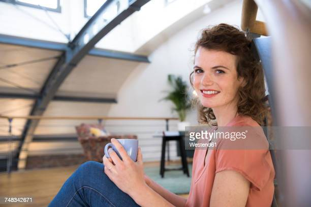 Portrait of smiling woman having a coffee break in modern office