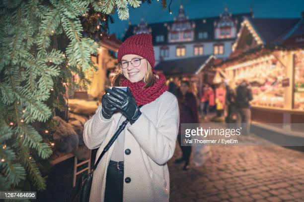 portrait of smiling woman having coffee at city during winter - val thoermer stock-fotos und bilder