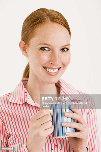 "portrait of smiling woman holding a coffee cup - ""compassionate eye"" fotografías e imágenes de stock"