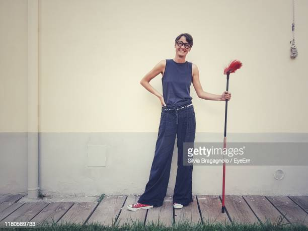 portrait of smiling woman holding broom while standing against wall - broom stock pictures, royalty-free photos & images