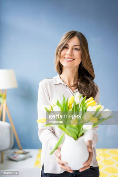 portrait of smiling woman holding bunch of tulips in a jar - 40 44 jaar stock pictures, royalty-free photos & images