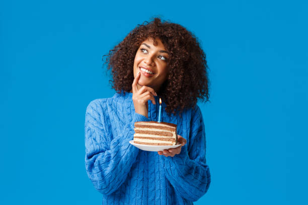 Portrait of smiling woman holding cake against blue background