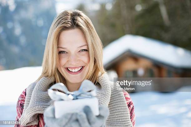 Porträt der lächelnde Frau hält Weihnachtsgeschenk vor cab