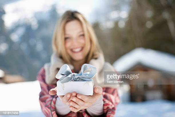 Portrait of smiling woman holding Christmas gift in front of cabin