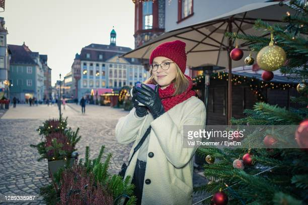 portrait of smiling woman holding coffee cup standing outdoors - val thoermer stock-fotos und bilder