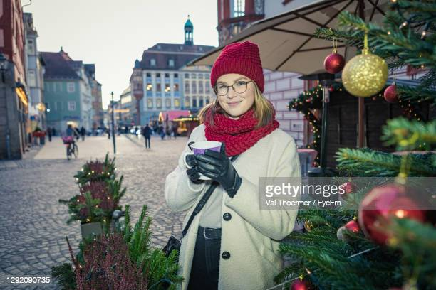 portrait of smiling woman holding drink on street in city during christmas - val thoermer stock-fotos und bilder