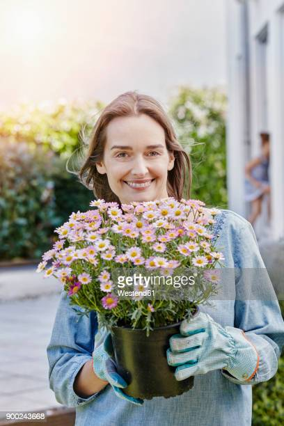 Portrait of smiling woman holding flowerpot in garden